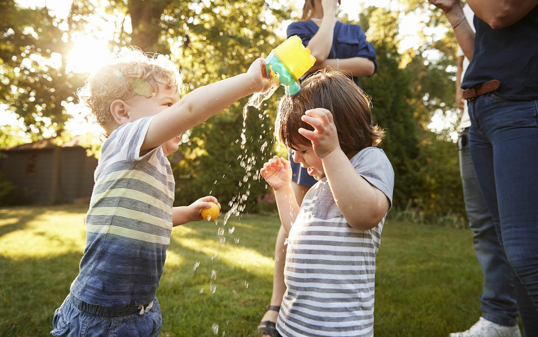 niño-jugar-con-agua-en-el-jardin