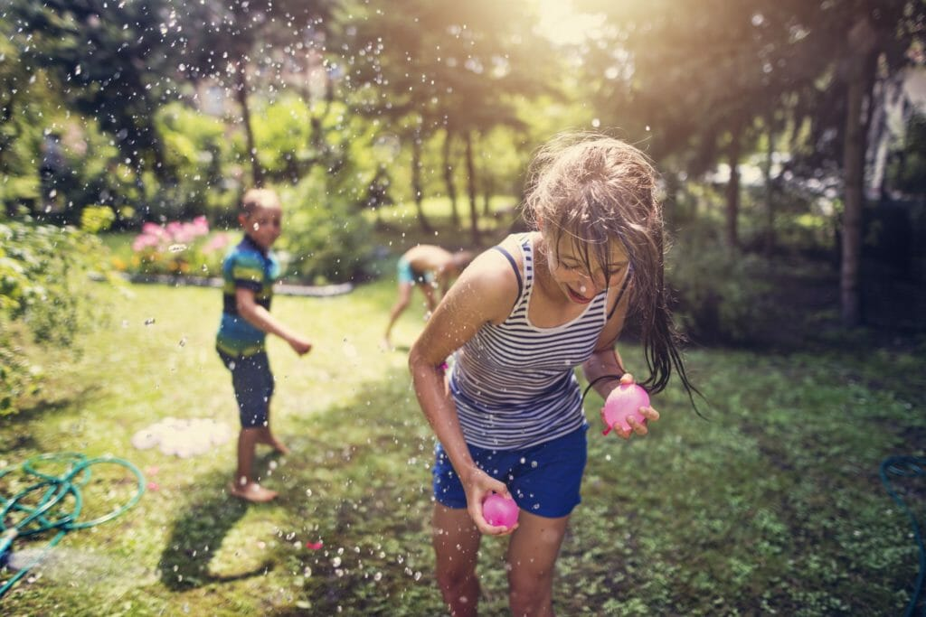 niños y niñas jugando a guerra de globos de agua