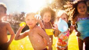 niños-y-niñas-jugando-con-globos-de-agua-verano